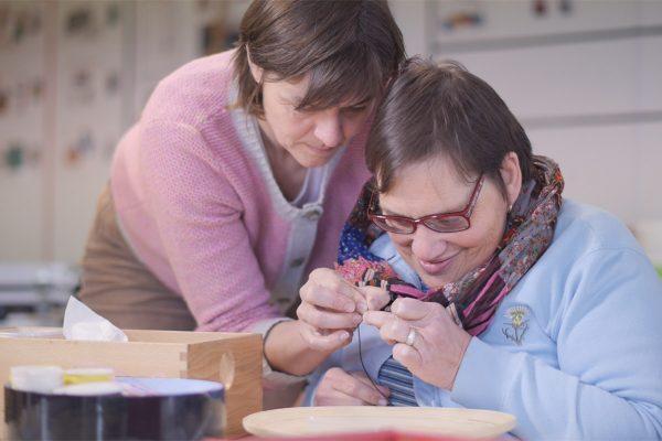 Eine Frau hilft einer betreuten Person beim Basteln