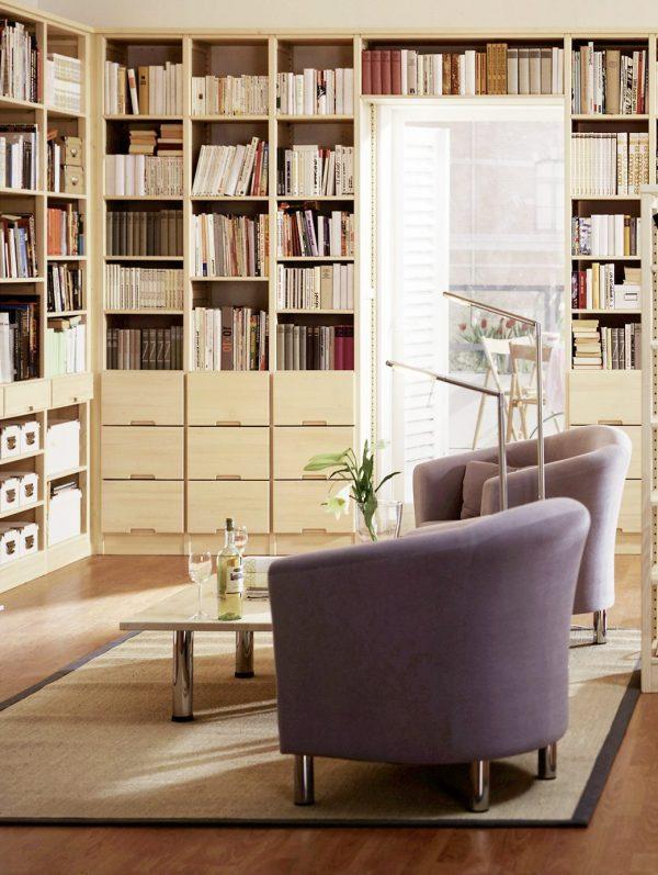Ein Zimmer in dem IWELO Regale sthen, die mit jeder Menge Bücher gefüllt sind und in der Mitte des Raums stehen zwei Sessel und ein Tisch