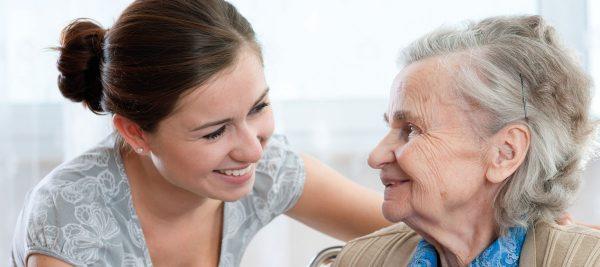 Eine ältere Frau lächelt einer hinter ihr stehenden jungen Frau ins Gesicht.