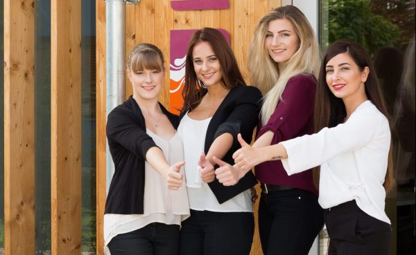 Vier junge Frauen zeigen mit dem Daumen nach oben