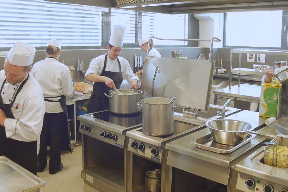 Ein Küchenteam in einer Großküche beim Kochen