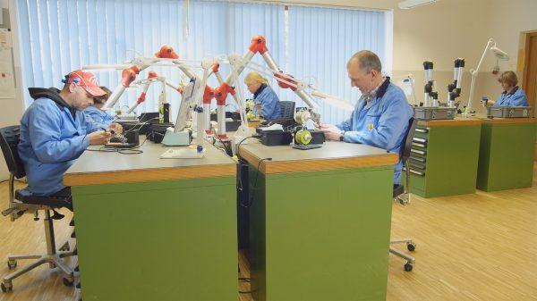 MEnschen arbeiten an Elektroarbeitsplätzen