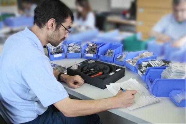 Ein Mann sitzt an einem Arbeitstisch und konfektioniert Bauteile