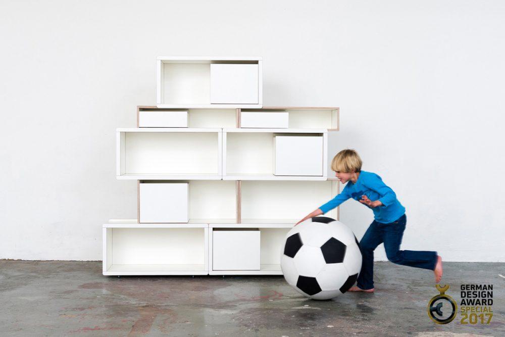Weißes Brick for Kids Regalsystem mit einem Jungen der mit einem rießigen Ball spielt
