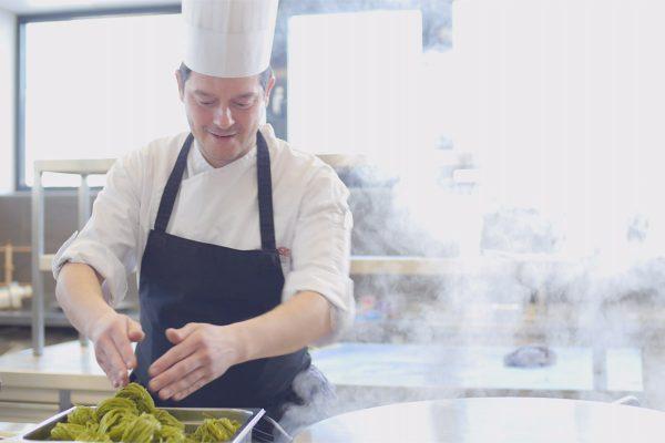 Ein Koch beim Zubereiten von einer Mahlzeit
