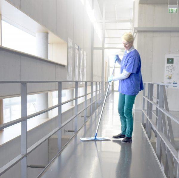 Eine frau beim reinigen eines fussbodens