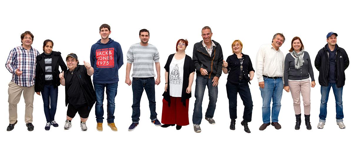 Ein Gruppe von Menschen stehen bunt durcheinander und blicken in die Kamera und stellen das Logo der Elf Freunde nach