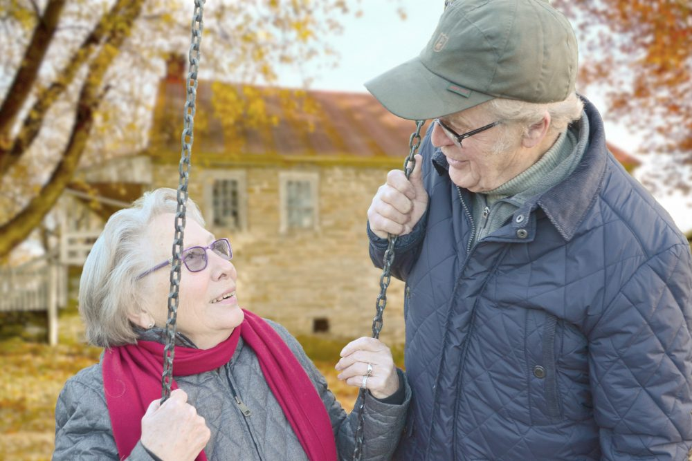 ältere Frau und Mann betrachten sich an einer Schaukel