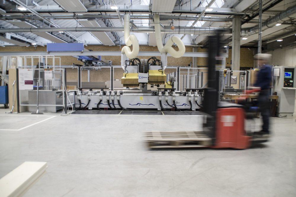Stapler fährt vor einem CNC-Holzearbeitungszentrum