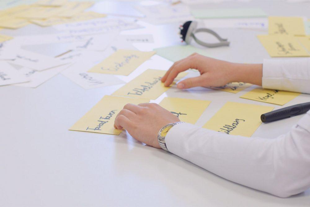 zwei hände sortieren beschriftete moderationskarten auf einem tisch