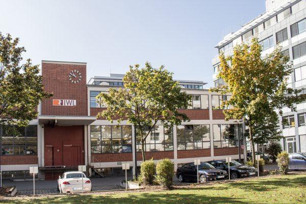 Blick auf das Backsteingebäude der IWL München mit grünen Bäumen davor