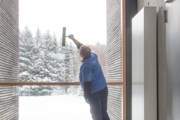 Ein Mann reinigt ein großes Fenster