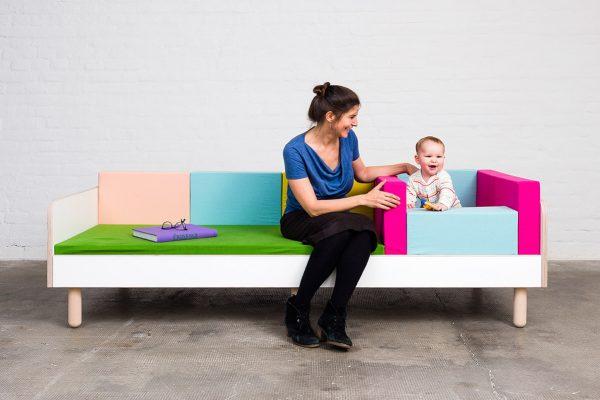 Ein Frau sitzt mit einem Baby lächelnd auf dem growing bed