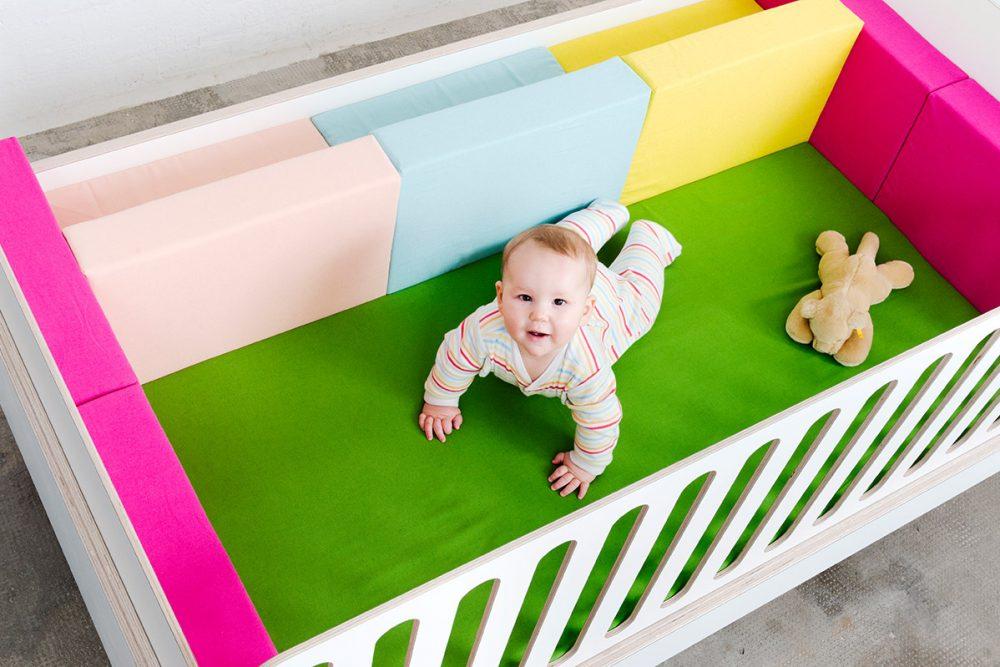 Ein Baby liegt auf dem growing Bed mit einem Teddybär