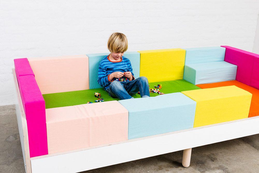 Ein Junge sitzt auf dem Growing Bed und spielt mit Lego