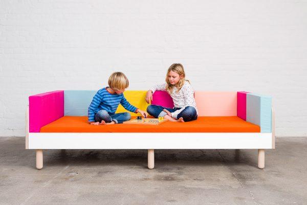Ein Junge und ein Mädchen sitzen auf dem growing bed und spielen ein Brettspiel