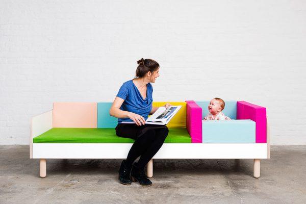 Eine Frau lächelt ein Baby an während beide auf dem growing bed sitzen