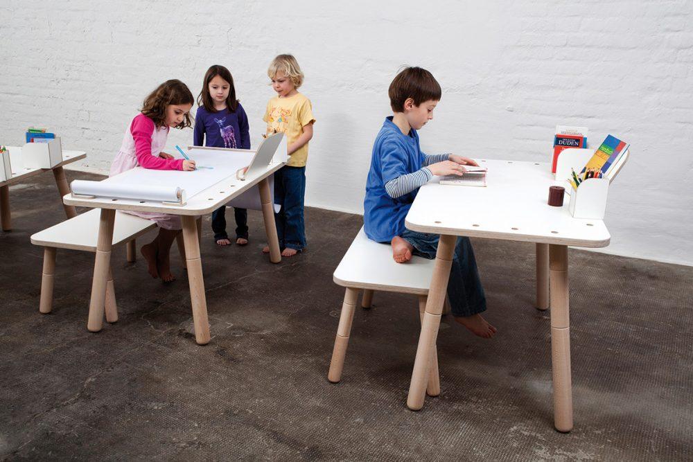 Ein Mädchen malt etwas an einem growing table, ein Junge ließt und zwei weitere Kinder schauen dabei zu