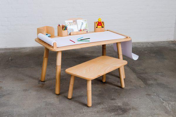 Growing Table mit einem Hocker davor und Schreibpapier mit Stiften