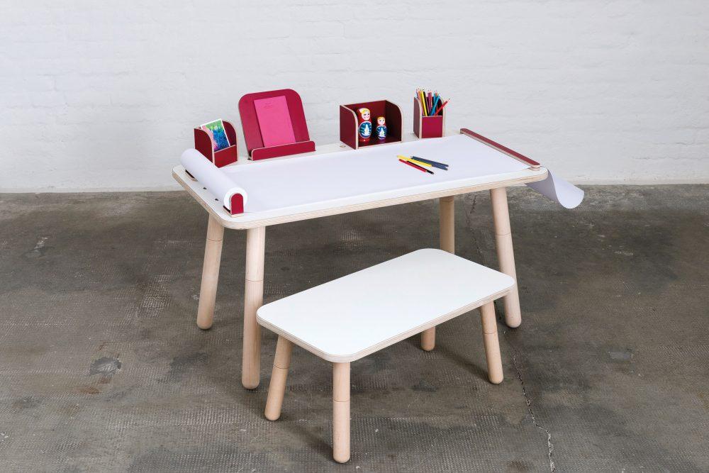 Ein weißer growing table mit einer Papierrolle und Stiften und einem Stuhl