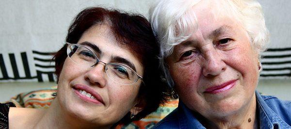 Zwei ältere Frauen lehnen ihre Köpfe aneinander und Blicken in die Kamera