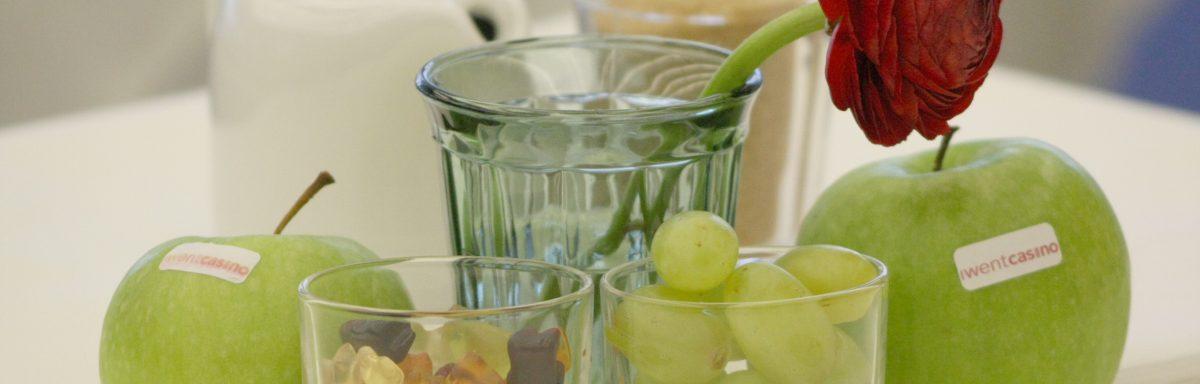 Zwei grüne Äpfel mit iwentcasino-Aufschrift und ein Glas Gummibärchen neben einem Glas Weintrauben, dahinter eine Blume im Glas