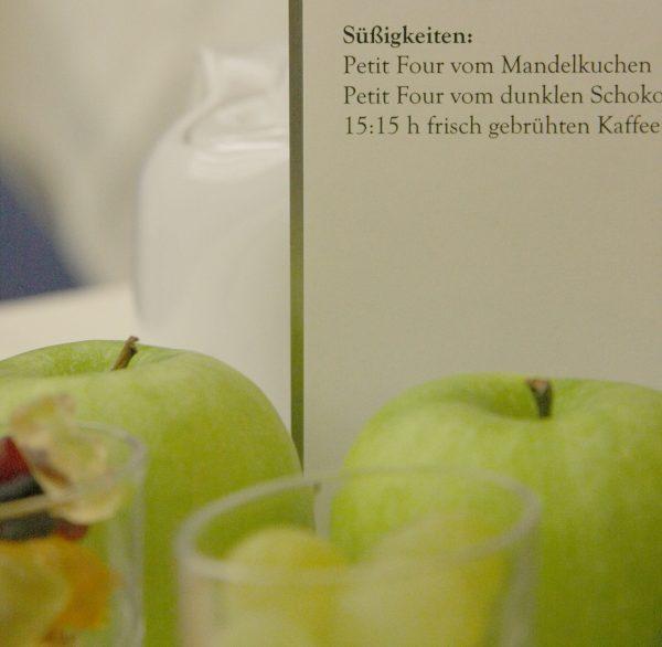 Zwei Äpfel vor einer stehenden Speisekarte; dahinter eine weiße Kanne