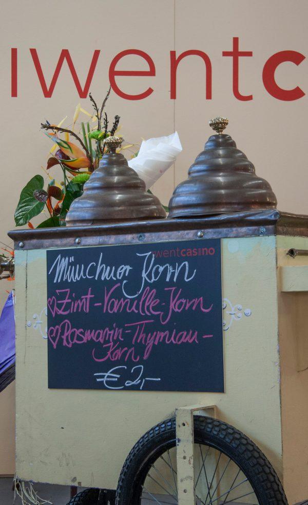 """Ein alter Handschiebewagen zum Popkornverkauf mit Tafelaufschrift """"Münchner Korn, Zimt-Vanille und Rosmarin-Thymian-Korn"""
