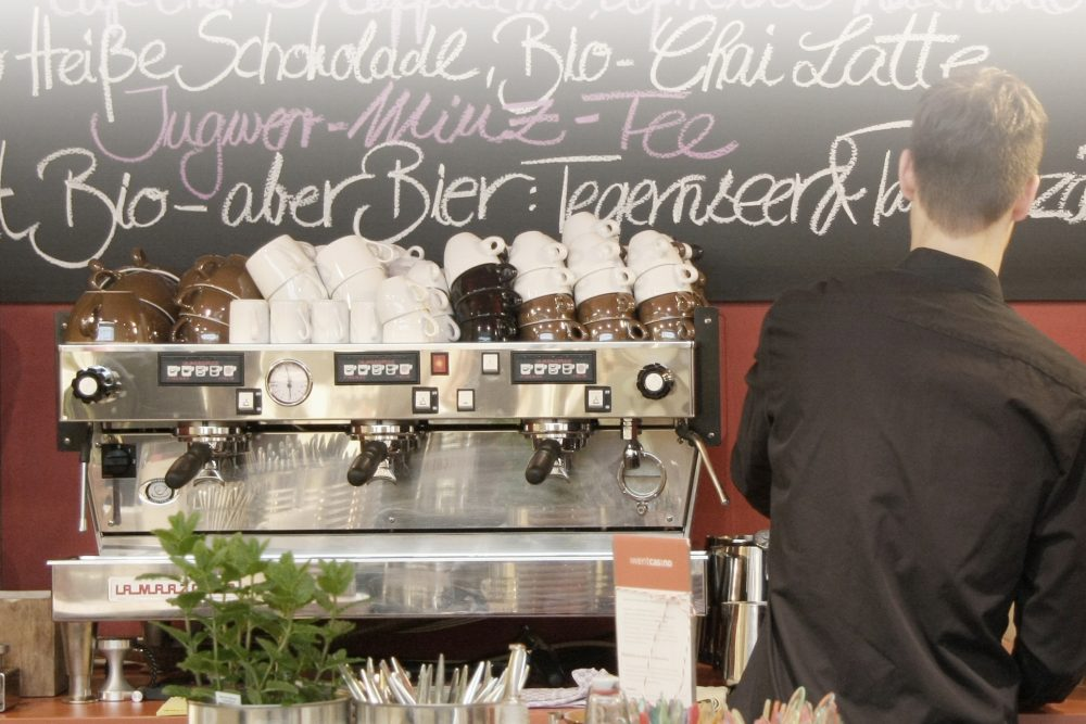 Ein Barista steht neben einer Kaffeemaschine und blickt auf die Tafel an der Wand