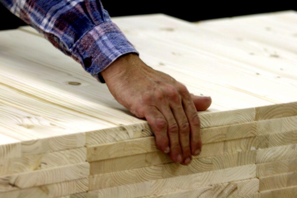 Eine Hand die Holzbretter gerade rückt