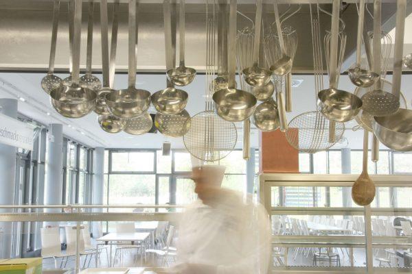 Koch hinter einer Reihe hängender Schöpflöffel