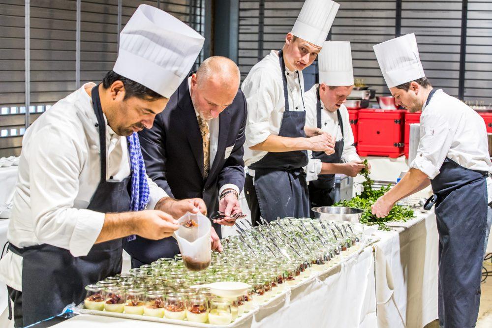 5 Köche stehen an einem Tisch und bereiten Desserts für ein Buffet vor.
