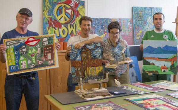 Eine Künstlergruppe bestehend aus drei Männern und einer Frau zeigen ihre Kunstwerke in Form von Bildern und Skulpturen