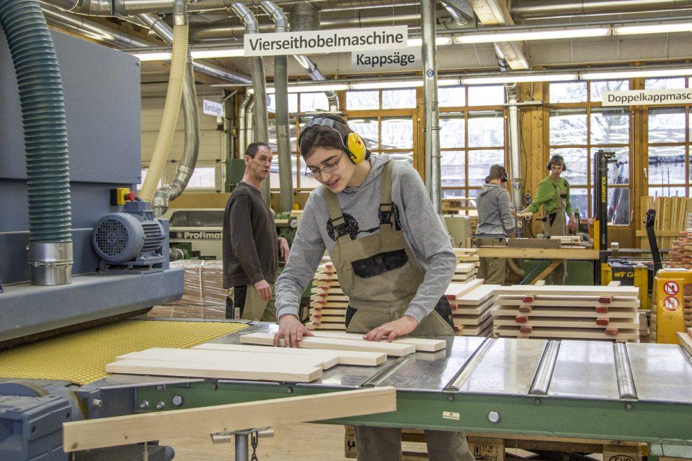 Eine Schreinerin arbeitet an einer Schleifmaschine