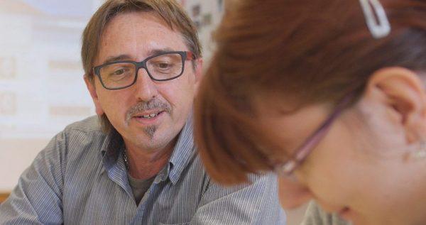 Ein Mann schaut einer Frau beim erarbeiten eines Dokumentes zu