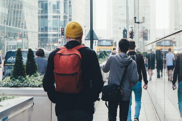 Drei Männer laufen durch eine Großstadt.