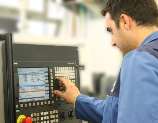 Ein Mann programmiert eine CNC-Maschine