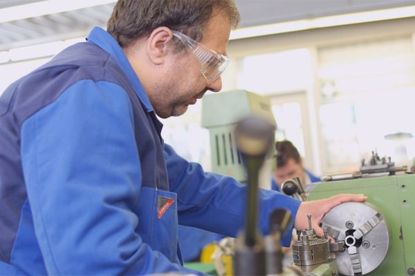 Ein Mann der konzentriert an einer Maschine arbeitet