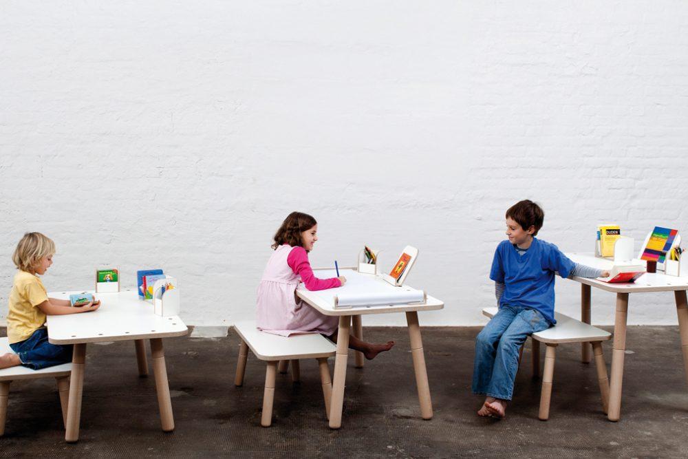 Drei Kinder sitzen an dem Growing Table und spielen, malen und unterhalten sich