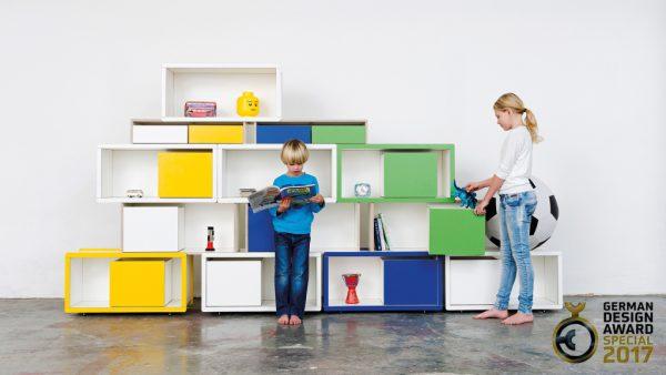 Brick for Kids Regal mit einem lesenden Jungen und einem spielenden Mädchen im Vordergrund