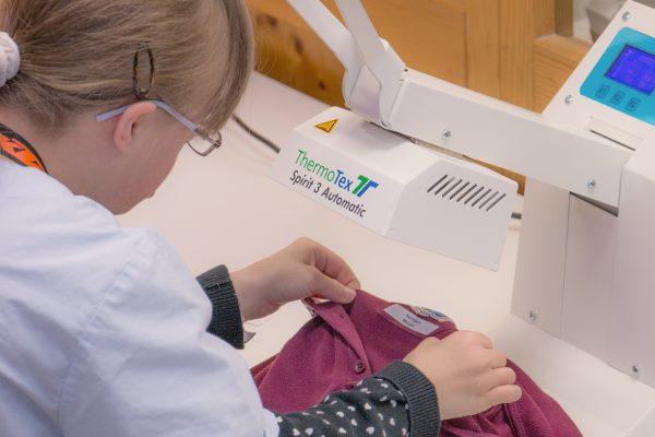 Eine junge Frau näht ein Namensetikett an ein T-Shirt