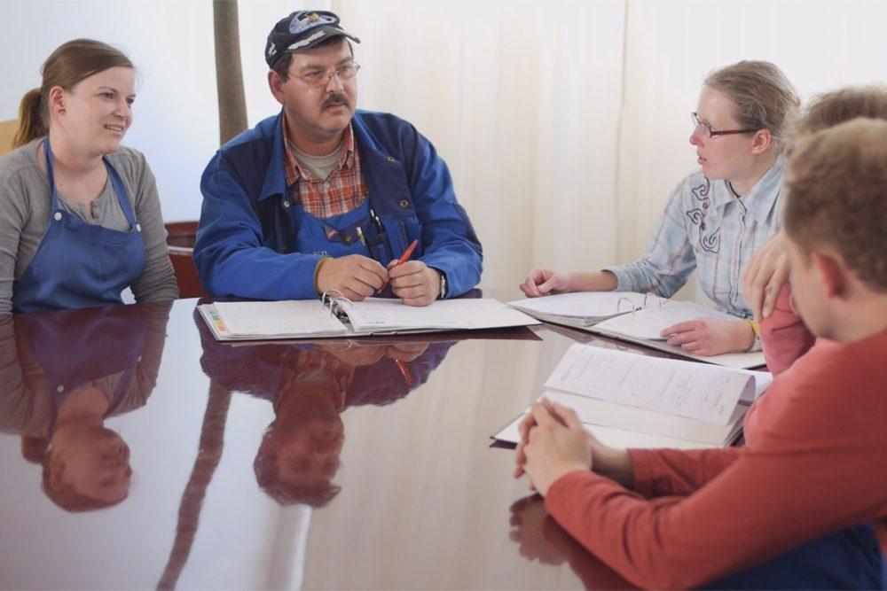 Mehrere Personen sitzen an einem Tisch und sprechen
