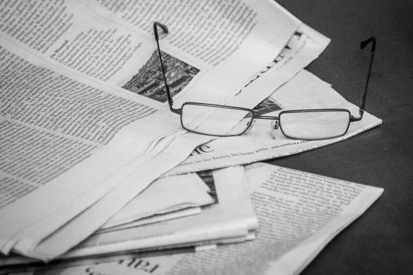 Zeitungen mit einer darauf liegenden Brille