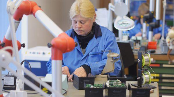 Frau arbeitet an einem Lötarbeitsplatz