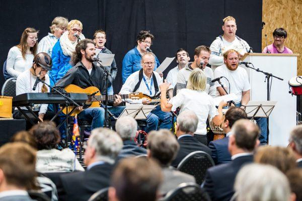 Menschen musizieren miteinander auf einer Bühne