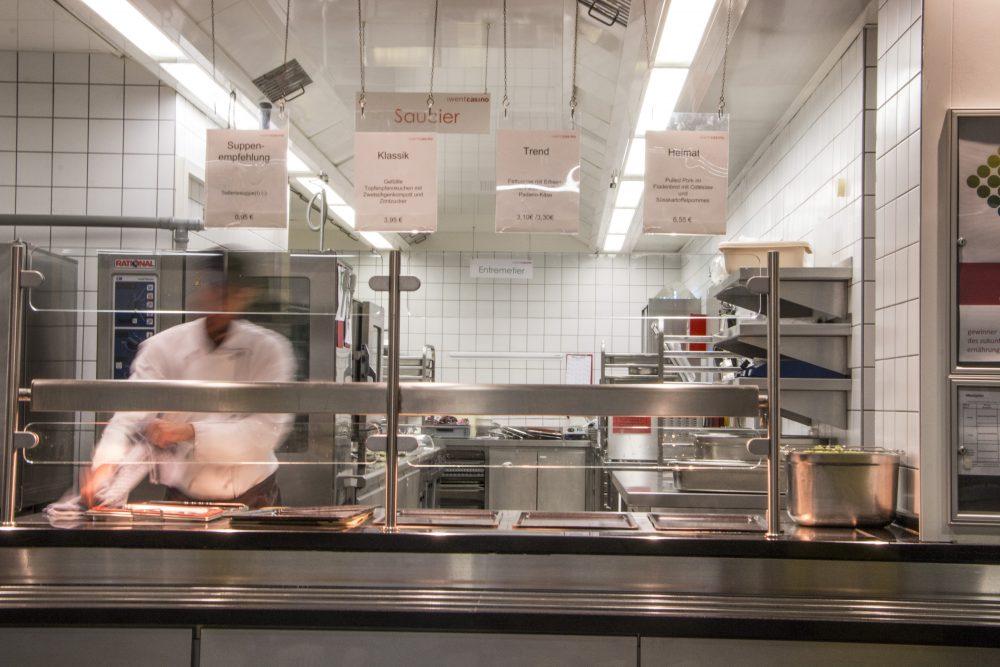 Ein Koch bereitet die Ausgabetheke für Speisen in einer Kantine vor