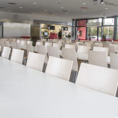 Blick in eine Schulmensa mit leeren Tisch- und Stuhlreihen