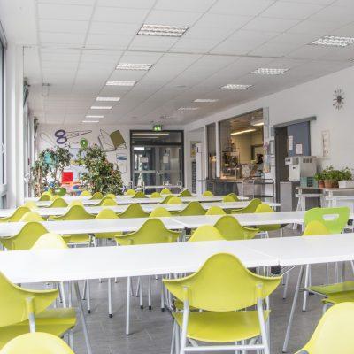 Blick in eine Schulmensa mit grünen Stühlen und Tischreihen