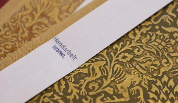 Goldbrauner Büchrücken mit der Aufschrift Handarbeit und dem Logo der IWL