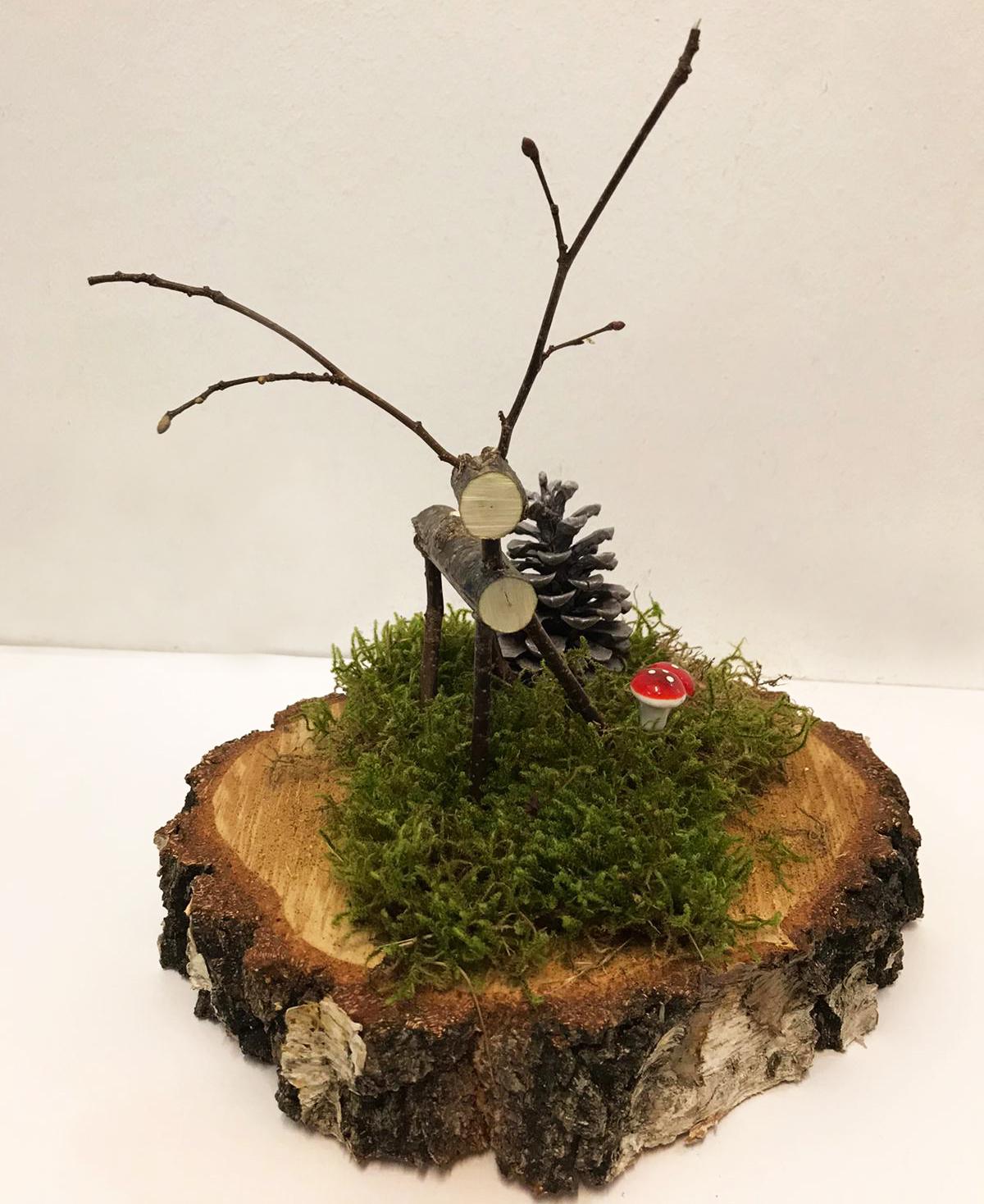 Ein Hirsch aus Holz auf einem Moos Beet